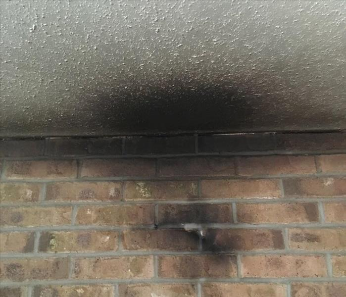 A brick wall and ceiling is black with fire damage.