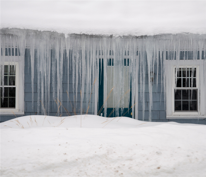 Picture shows a blue home with an exuberant amount of snow on the roof and long icicles hanging off the roof.