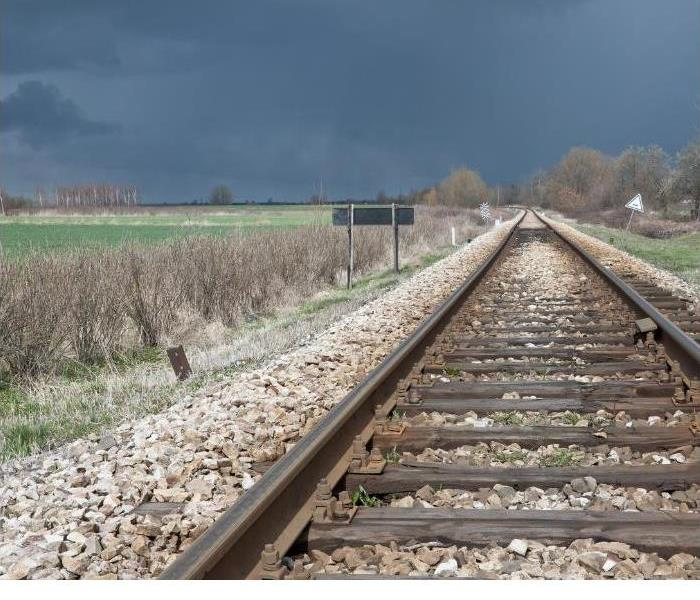 Picture shows a set of railroad tracks with a dark storm brewing in the process